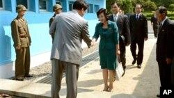 ေတာင္ကိုရီးယား ျပန္လည္ေပါင္းစည္းေရးဝန္ႀကီး Kim Song Hye (လယ္)၊ ေျမာက္ကိုရီးယား ကိုယ္စားလွယ္တို႔ ေတာင္နဲ႔ေျမာက္ ပိုင္းျခားထားေသာ စစ္မဲ့ဇုန္နယ္ေျမစည္းကို မျဖတ္ခင္ ႏႈတ္ဆက္ေနၾကစဥ္။ (ဇြန္လ ၉ ရက္၊ ၂၀၁၃။)