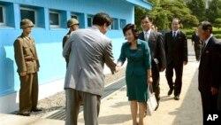 Šef severno korejske delegacije se rukuje sa neidentifikovanim južno korejskim funkcionerom pre prelaskavojne demarkacione linije, 9 juni, 2013.