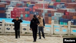 FILE - Security guards walk in front of containers at the Yangshan Deep Water Port in Shanghai, China, April 24, 2018.