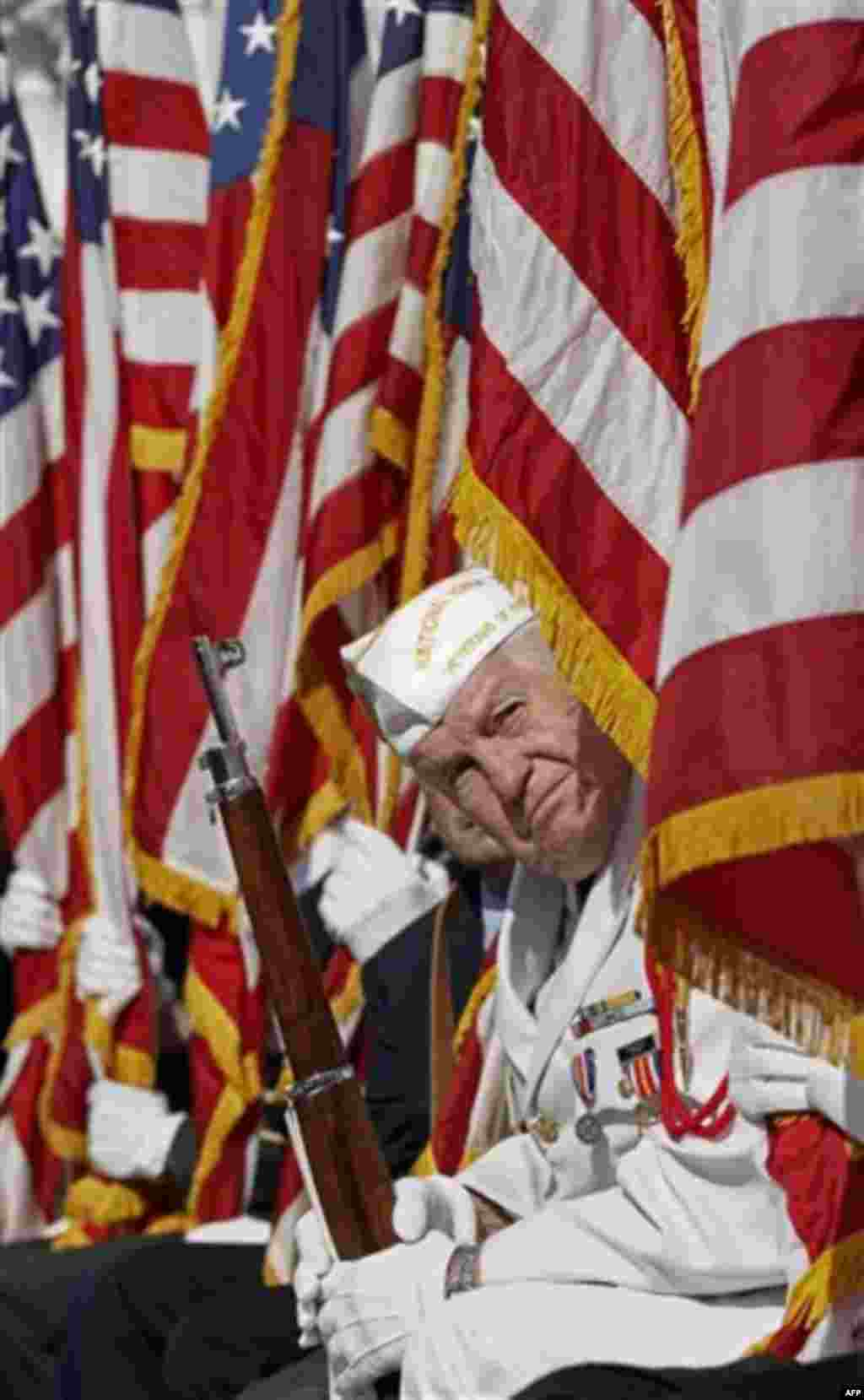 A member of the National Honor Guard looks out from behind an American flag to listen to President Barack Obama as he speaks during a Veteran�s Day ceremony at Arlington National Cemetery in Arlington, Va., Friday, Nov. 11, 2011. (AP Photo/Pablo Martinez