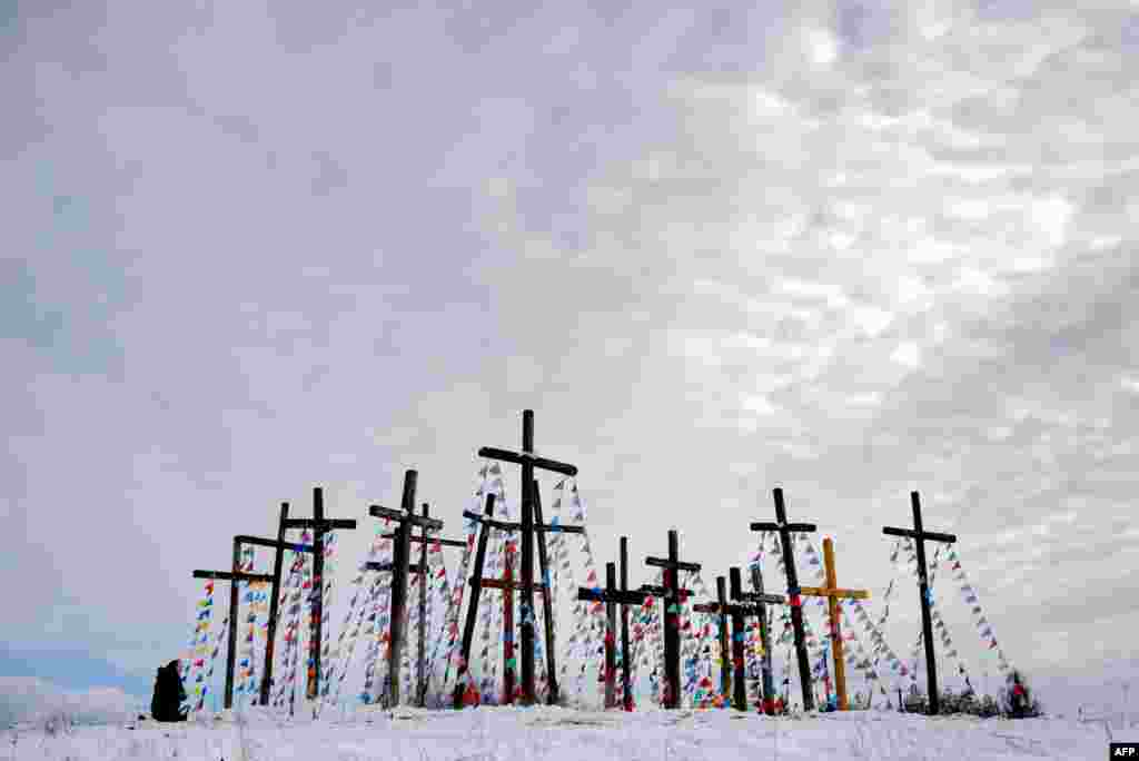 A woman prays on a hill with wooden crosses as she celebrates Palm Sunday in the town of Oshmiany, some 130 kilometers northwest of Minsk, Belarus.