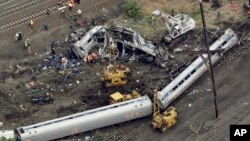 FILE- Emergency personnel work at the scene of a derailment in Philadelphia of an Amtrak train headed to New York, May 13, 2015.