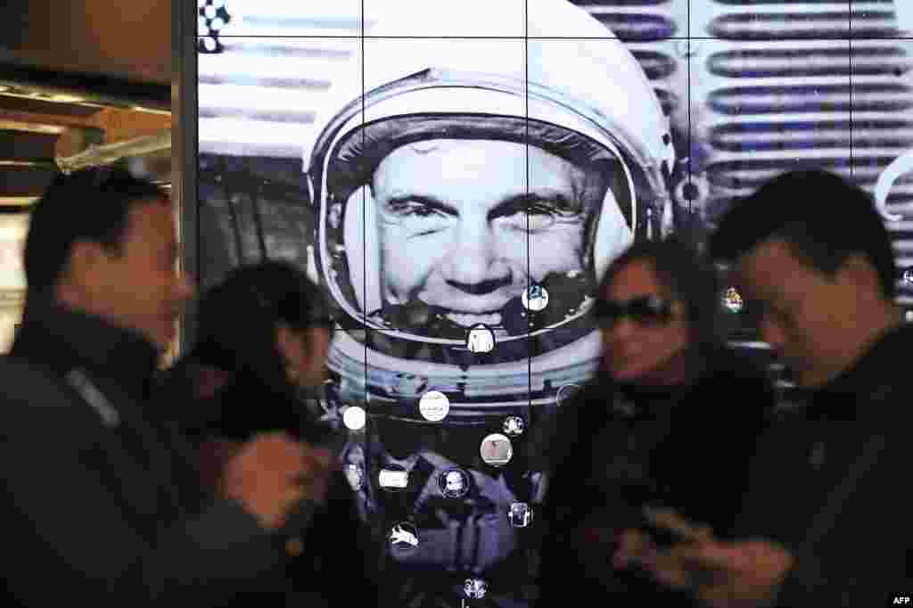 Tourists gather near a tribute to former astronaut and U.S. Senator John Glenn, at the National Air and Space Museum, in Washington, D.C. Glenn, who passed away Dec. 8, was the first American to orbit the earth.