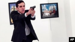 A gunman gestures after shooting the Russian Ambassador to Turkey, Andrei Karlov, at a photo gallery in Ankara, Turkey, Dec. 19, 2016.