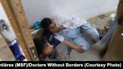 Các nhân viên của tổ chức Y sĩ Không biên giới bị sốc ngồi tại một phần của toà nhà không bị phá huỷ bởi vụ không kích ở Kunduz, ngày 3/10/2015.