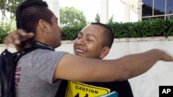 Students Irvis Orozco, left, and Jorge Gutierrez hug outside the US Citizenship and Immigration Services at the Federal Building in Los Angeles Wednesday, Aug. 15, 2012.