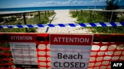 A closed beach signage is seen at Coolangatta Beach on the Queensland - New South Wales border in Brisbane on April 15, 2020. - A state border that bisects Australia's neighbouring beachside towns of Coolangatta and Tweed Heads has rarely troubled…