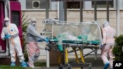 Un patient dans une unité de bioconfinement est transporté sur une civière depuis une ambulance arrivée à l'hôpital Columbus Covid 2 à Rome (Italie), le 17 mars 2020. (Photo: AP)