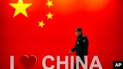 """安保人员从中国国旗和""""我爱中国""""标志旁走过。"""