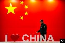 """保安人员在北京一个博览会上走过带有中国国旗显示屏和标有""""我爱中国""""的标牌。(2019年10月31日)"""