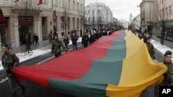 """Lithuanians march during a celebration of the 20th anniversary of the """"Battle for the Freedom of Nations"""" carrying a 200m long sash in the Lithuanian flag colors from the Cathedral Square to the Independence Square in Vilnius, Lithuania, 13 Jan 2011"""