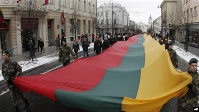 "Lithuanians march during a celebration of the 20th anniversary of the  ""Battle for the Freedom of Nations"" carrying  a 200m long  sash  in the Lithuanian flag colors from the Cathedral Square to the Independence Square in Vilnius, Lithuania, 13 Jan 2011"