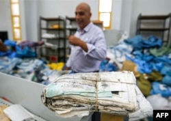 A picture taken on Aug. 14, 2018 shows a stack stack of letters and postcards, among many items of undelivered mail dating as far back as 2010 which has been withheld by Israel.