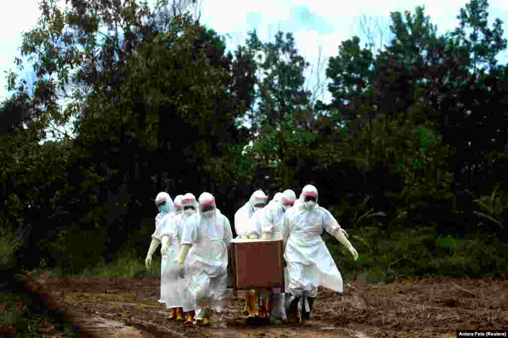 Municipal workers wearing protective gear bury a victim of the coronavirus disease (COVID-19) at a cemetery in Tarakan, North Kalimantan Province, Indonesia.