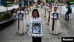 Para pengunjuk rasa memegang potret para perempuan Korea yang dipaksa menjadi budak seks oleh tentara Jepang selama Perang Dunia Kedua, dalam upacara penghormatan bagi Lee Yong-nyeo, di pusat Seoul (14/8). Lee, salah seorang mantan budak seks tentara Jepang jaman PD II, dilaporkan meninggal dunia hari Minggu (11/8).