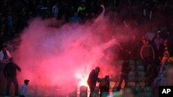 Flares are thrown in the stadium during deadly clashes that erupted after a football match between Egypt's Al-Ahly and Al-Masry teams in Port Said, Egypt, February 1, 2012.
