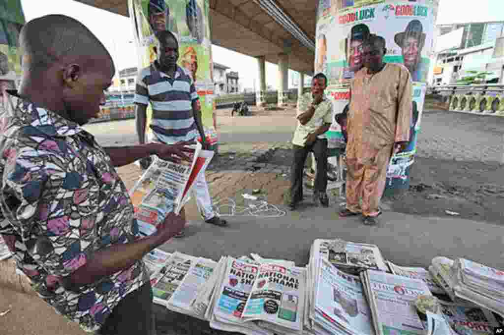 "An Unidentified man reads a Newspaper with headlines ""National Shame"" after the election was postponed yesterday by Attahiru Jega Electoral Commission Chairman, Lagos, Nigeria, Sunday, April 3, 2011. Nigeria postponed its National Assembly elections Satu"