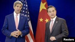 El ministro de exteriores chino, Wang Yi escucha al secretario de Estado, John Kerry, durante una conversación bilateral en Kuala Lumpur, Malasia.