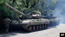 FILE - Pro-Russian troops prepare to travel in a tank on a road near the town of Yanakiyevo, Donetsk region, eastern Ukraine, June 20, 2014.