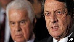 FILE - Cyprus' president Nicos Anastasiades (r) and Turkish Cypriot leader Dervis Eroglu, talk to the media after their meeting in the divided capital Nicosia.