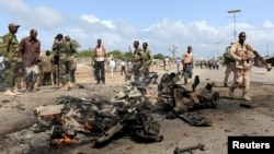 Somali government forces assess the scene of a suicide car explosion in Hodan district in the capital Mogadishu, June 24, 2015.