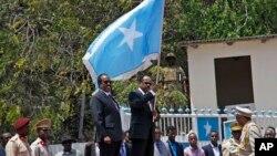 Le nouveau président somalien Mohamed Abdullahi Farmajo brandit le drapeau de la Somalie au cours de la cérémonie de la passation de pouvoir avec le président sortant du pays Hassan Sheikh Mohamud, au centre à gauche, à Mogadiscio, Somalie, 16 février 2017.