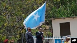 Somalia's President Mohamed Abdullahi Farmajo, center-right, holds a Somali flag during a handover ceremony at the presidential palace with former president Hassan Sheikh Mohamud, center-left, in Mogadishu, Somalia Thursday, Feb. 16, 2017.