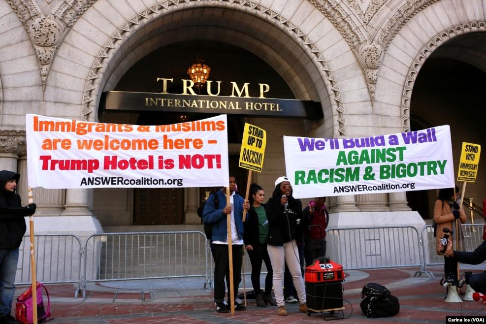"""在华盛顿,在川普新开张的豪华酒店前面,有人示威,标语上写着""""这里欢迎移民和穆斯林,不欢迎川普酒店""""""""对抗种族主义""""""""我们要筑墙阻挡种族主义"""""""