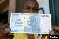 FILE - A black market foreign currency dealer displays the new $1 million banknote worth $7 on the streets of Harare, October 6, 2008.