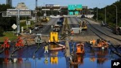 Radnici čiste dio autoputa u Filadelfiji posle poplava izazvanih ostacima uragana Ida (Foto: AP/Matt Rourke)
