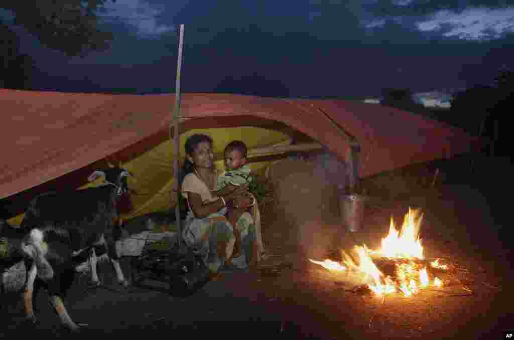 Một phụ nữ nạn nhân lũ lụt cùng đứa con nhỏ ngồi bên ngoài một căn lều tạm trên một con đường tại Jhargaon, bang Assam, ngày 2 tháng 7 năm 2012