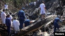老撾的救援人員在飛機墜毀現場進行搜救工作。