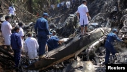 Rescue workers search an air force plane crash site near Nadee village, in Xiang Khouang province in the north of the country May 17, 2014. The Laos air force plane with 14 people on board, including the defence minister, has crashed in the north of the S