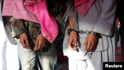 Two men in handcuffs, whom the police said belong to the Tehreek-e-Taliban Pakistan [TTP] group, are shown during a news conference at the Crime Investigation Department after their arrest, in Karachi, January 2013.
