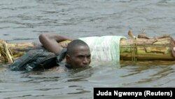 Un homme traverse à la nage la rivière Monserado à Monrovia, au Liberia, le 14 août 2003.