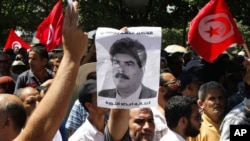 Supporters of the Islamist Ennahda movement demonstrate as they chants slogans and hold a picture of assassinated politician Mohamed Brahmi during a demonstration in Tunis, Tunisia, July 26, 2013.