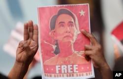Dân Myanmar ở Thái Lan mang ảnh của lãnh đạo Aung San Suu Kyi đi biểu tình, họ giơ 3 ngòn tay chào, biểu tượng phản kháng quân đảo chính, trước sứ quán Myanmar ở Bangkok, Thái Lan, ngày 8/2/2021.