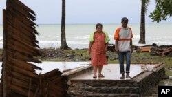 La sobreviviente del tsunami, Kusmiati, camina con su esposo Aden en una villa destruida por el tsunami en Carita, Indonesia, el miércoles 26 de diciembre de 2018.