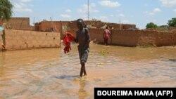Un enfant patauge dans l'eau dans une rue inondée du quartier de Kirkissoye à Niamey, le 3 septembre 2019.