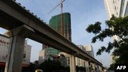 骑摩托车的人经过中国出资在河内修建的一处高架铁轨。(2014年9月12日资料照)