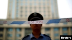 FILE - A police officer stands guard at the entrance to the Jinan Intermediate People's Court. While homosexuality is not illegal in China, same-sex marriage is not legal and same-sex couples do not have legal protections.
