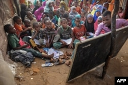 FILE - Displaced Somali children and teenagers are taught letters and numbers at a makeshift school at the Badbado IDP camp in Mogadishu, Somalia, June 25, 2018.