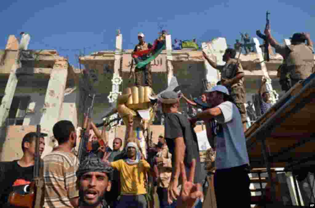 Rebels and their supporters celebrate around the iconic statue of a golden fist crushing a US military bomber outside Libyan leader Moammar Gadhafi's heavily damaged Bab al-Azizya compound in the centre of Tripoli on August 24, 2011