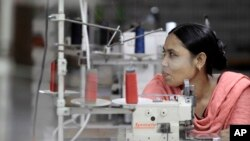 FILE - Bangladeshi garment worker Asma, who worked on the 4th floor of Rana Plaza garment factory that collapsed exactly a year ago, works at a factory meant to rehabilitate survivors of the accident, the worst in the history of the garment industry, in S