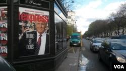 Un panneau publicitaire dans une rue parisienne reflète la réaction en France aux élections américaines, Paris, le 18 novembre 2016. (L. Bryant / VOA)