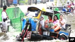 """People ride a modified """"tuk-tuk,"""" or motor tricycle taxi, through a flooded street in Bangkok, Thailand, November 7, 2011."""