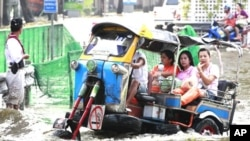 "People ride a modified ""tuk-tuk,"" or motor tricycle taxi, through a flooded street in Bangkok, Thailand, November 7, 2011."
