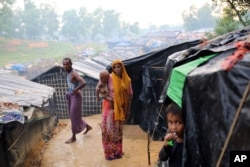 A Rohingya woman holds her child and stands at a makeshift camp near Kutupalong refugee camp in Cox's Bazar, Bangladesh, Oct. 3, 2017. More than half a million Rohingya have fled from Myanmar to Bangladesh in just over a month, the largest refugee crisis
