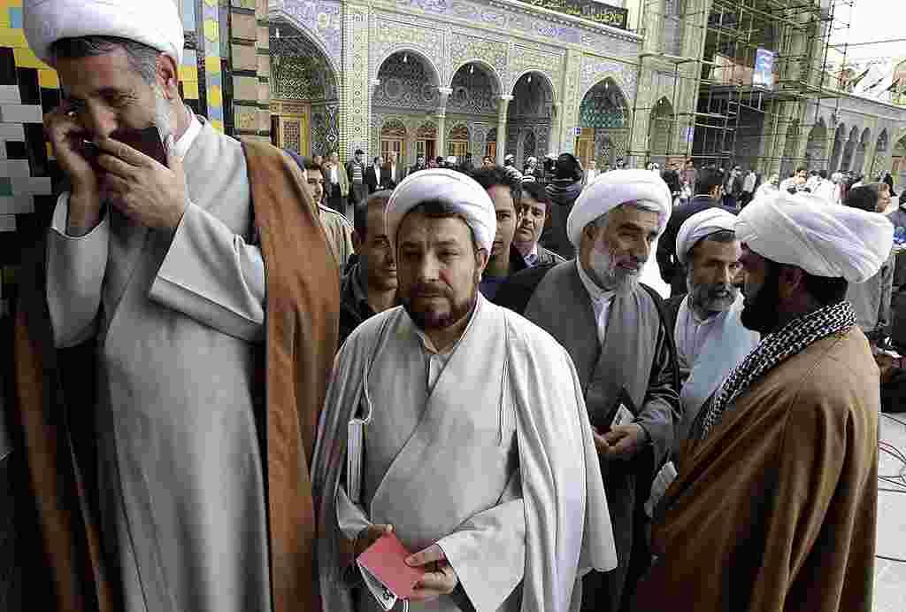 Mojtaba Zolnouri, un ex oficial de la Guardia Revolucionaria, a la derecha en la foto habla en su teléfono mientras otros clérigos esperan para emitir su voto.