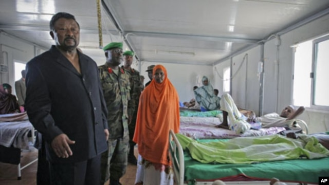 Jean Ping (L), chairman of the Commission of the African Union, visits wounded Transitional Federal Government soldiers at the African Union Mission in Somalia Level II hospital, at the operation's headquarters in Mogadishu, Somalia, August 20, 2011. (fil
